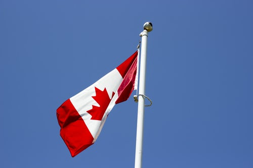 Flag of Canada on a pole blowing in the wind